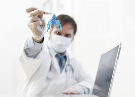 Doctor holding a fake bug pulled from a computer